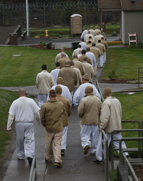 Inmates walk at Larch Correctional Facility Friday, April 20, 2012, in Yacolt, Wash.  The Cuddly Catz program at the Larch Correctional Facility, a minimum-security prison is several months old, but inmates say they've already noticed a difference in the cats and themselves. The program began in cooperation with a local animal shelter. It has grown to include two cats and four inmates, and the prison plans to add four more cats. (AP Photo/Rick Bowmer)