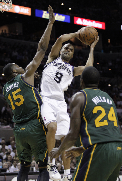 San Antonio Spurs' Tony Parker (9), of France, works between Utah Jazz's Derrick Favors (15) and Paul Millsap (24) during the third quarter of Game 2 of a first-round NBA basketball playoff series, Wednesday, May 2, 2012, in San Antonio. The Spurs won 114-83. (AP Photo/Eric Gay)