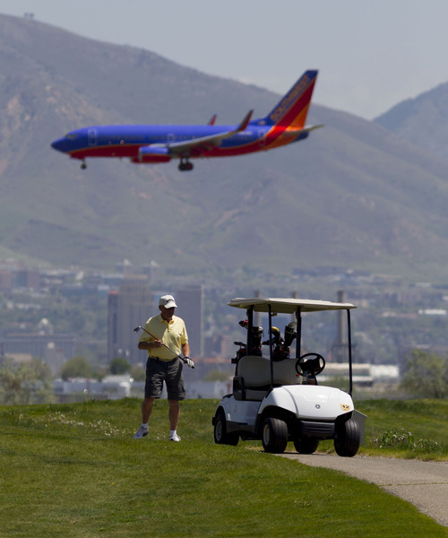Trent Nelson  |  The Salt Lake Tribune A Southwest Airlines jet flies over golfer Bob Newsom and Salt Lake City's Wingpointe golf course Wednesday, May 2, 2012.  A demand from the FAA could cause a dramatic increase in Wingpointe's lease.