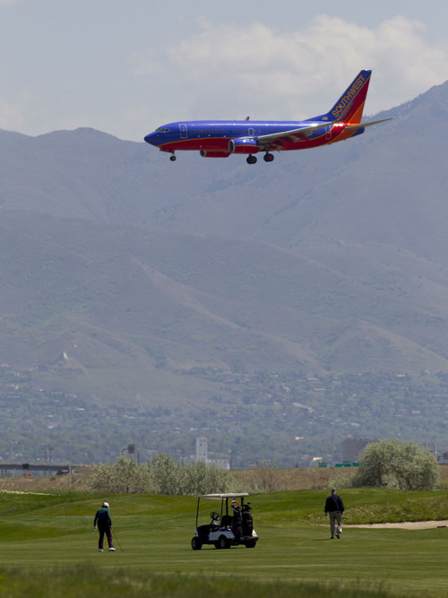 Trent Nelson  |  The Salt Lake Tribune A Southwest Airlines jet passes over golfers on the 9th hole at Salt Lake City's Wingpointe golf course Wednesday, May 2, 2012.  A demand from the FAA could cause a dramatic increase in Wingpointe's lease.