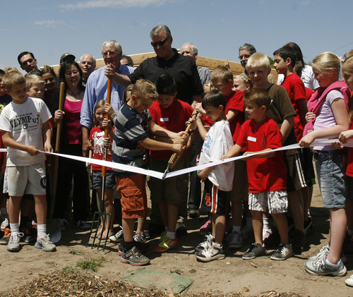 Rick Egan  | The Salt Lake Tribune   Mayor Peter Carroon with the help of tudents from Driggs Elementary School, cut the ribbon during the grand opening of the community garden in Holladay,  Friday, May 4, 2012.  The Mount Olympus Garden is a cooperative venture for Howard R. Driggs Elementary School, Olympus Junior High School, Salt Lake City, Holladay City, Salt Lake County, and New Roots of Utah in partnership with the International Rescue Committee.