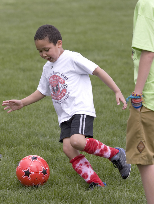 Paul Fraughton | The Salt Lake Tribune Charlie Cunningham, with a smile on his face, chases after the soccer ball. Charlie joined other kids with autism at a soccer clinic run by the RedDevils Soccer Club at the Carmen B. Pingree School and Sunnyside Park in Salt Lake City.   Thursday, May 3, 2012