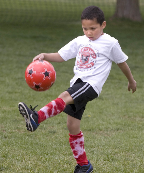 A Little Kid Kicking A Soccer Ball