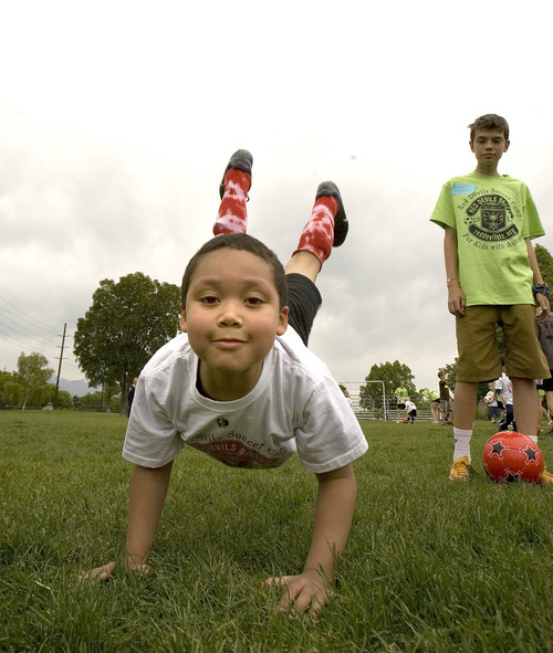 Paul Fraughton | The Salt Lake Tribune  Auden  Winchester, a volunteer mentor watches as Charlie Cunningham takes a break from soccer to do some impromptu headstands and cartwheels. Charlie joined other kids with autism at a soccer clinic run by the RedDevils Soccer Club at the Carmen B. Pingree School and Sunnyside Park in Salt Lake City.   Thursday, May 3, 2012