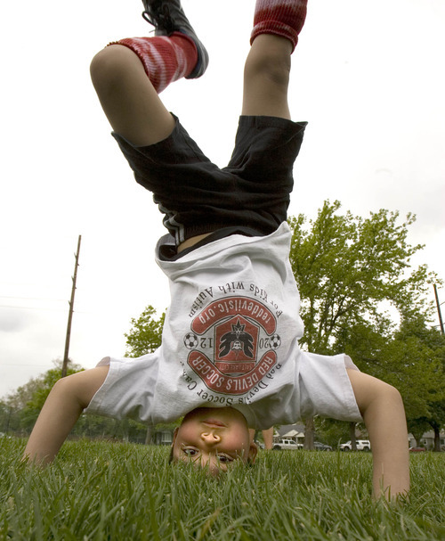 Paul Fraughton | The Salt Lake Tribune Charlie Cunningham takes a break from soccer to do some impromptu headstands and cartwheels. Charlie joined other kids with autism at a soccer clinic run by the RedDevils Soccer Club at the Carmen B. Pingree School and Sunnyside Park in Salt Lake City.   Thursday, May 3, 2012