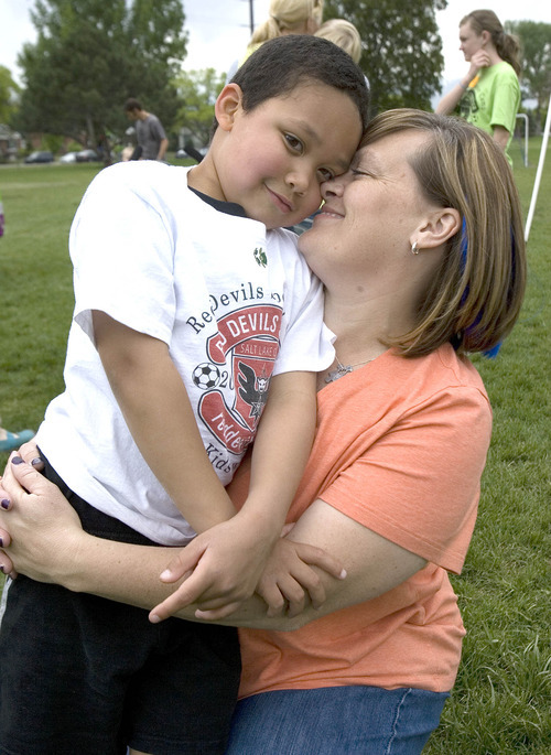 Paul Fraughton | The Salt Lake Tribune  Taking a break from the activities of the soccer camp. Charlie gets a hug from his mom Jen Cunningham.  Thursday, May 3, 2012