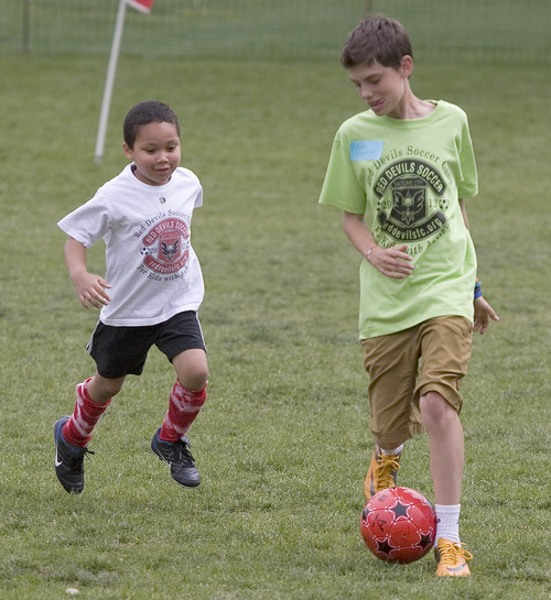 Paul Fraughton | The Salt Lake Tribune Charlie Cunningham plays some one on one soccer with one of his mentors Auden  Winchester.  Charlie joined other kids with autism at a soccer clinic run by the RedDevils Soccer Club at the Carmen B. Pingree School and Sunnyside Park in Salt Lake City.   Thursday, May 3, 2012