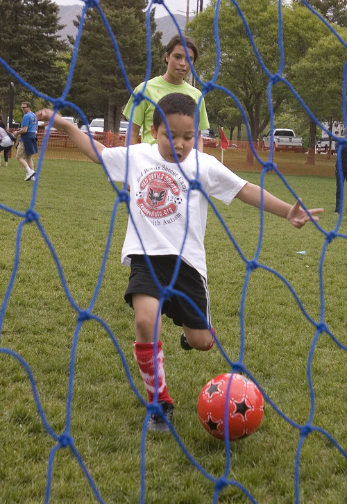 Paul Fraughton | The Salt Lake Tribune Parker Winchester, a volunteer mentor watches as Charlie Cunningham kicks the ball into the net. Charlie joined other kids with autism at a soccer clinic run by the RedDevils Soccer Club at the Carmen B. Pingree School and Sunnyside Park in Salt Lake City.   Thursday, May 3, 2012