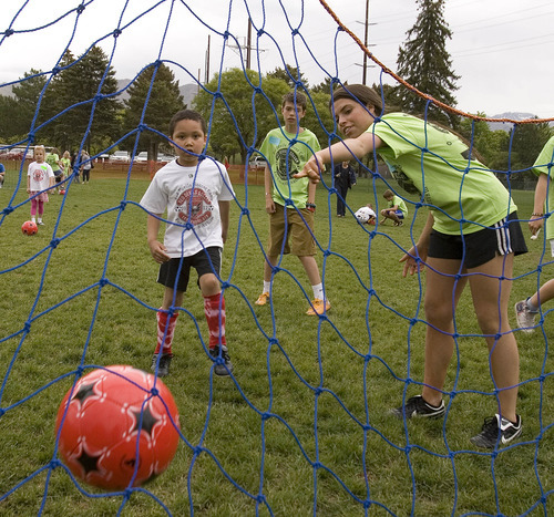 Paul Fraughton | The Salt Lake Tribune Parker Winchester, right and Auden Winchester,  volunteer mentors, watch as Charlie Cunningham kicks the ball into the net. Charlie joined other kids with autism at a soccer clinic run by the RedDevils Soccer Club at the Carmen B. Pingree School and Sunnyside Park in Salt Lake City.   Thursday, May 3, 2012