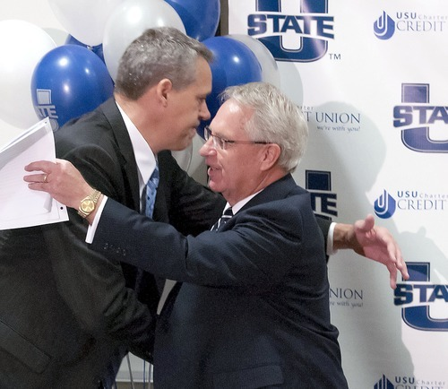 Athletics Director Scott Barnes left, hugs President Stan Albrecht during a press conference, Friday, announcing that Utah State University will be joining the Mountain West Conference. (AP Photo/The Herald Journal, Eli Lucero)