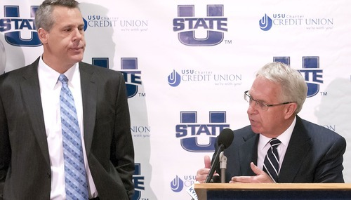 Athletics Director Scott Barnes left, listens as President Stan Albrecht speaks during a press conference, Friday, announcing that Utah State University will be joining the Mountain West Conference. (AP Photo/The Herald Journal, Eli Lucero)