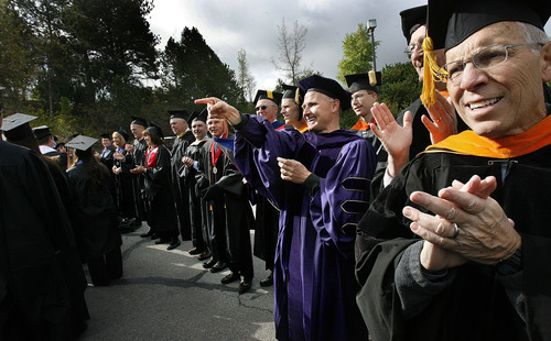 Scott Sommerdorf  |  The Salt Lake Tribune              A lineup of faculty including Paul Barr of the Engineering School, at center in purple robe, congratulate graduates as they file by during Utah State University's Commencement, Saturday, May 5, 2012.