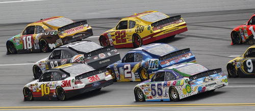 Greg Biffle (16) drives in a pack with Kyle Busch (18), AJ Allmendinger (22), Brad Keselowski (2) and Mark Martin (55) during the NASCAR Sprint Cup Series auto race at Talladega Superspeedway in Talladega, Ala., Sunday, May 6, 2012. (AP Photo/Dave Martin)