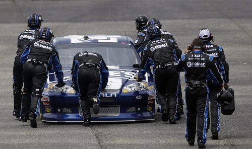 Pit crew members push Jimmie Johnson's car to the garage early in the NASCAR Sprint Cup Series auto race at Talladega Superspeedway in Talladega, Ala., Sunday, May 6, 2012. (AP Photo/Rainier Ehrhardt)