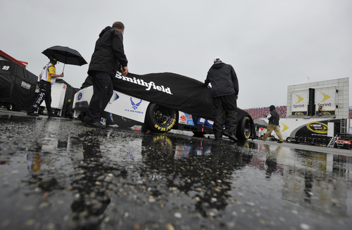 Pit crew members push the car of Aric Almirola through the rain at the Talladega Superspeedway in Talladega, Ala., Sunday, May 6, 2012. (AP Photo/Rainier Ehrhardt)