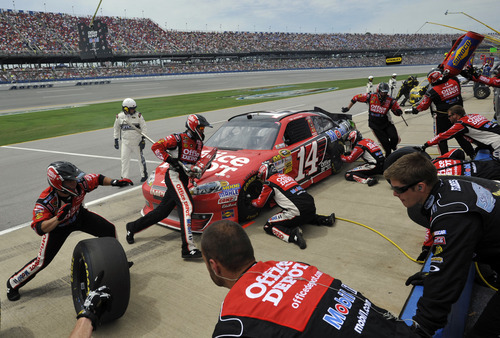 Tony Stewart (14) receives service at a pit stop during the NASCAR Sprint Cup Series auto race at Talladega Superspeedway in Talladega, Ala., Sunday, May 6, 2012. (AP Photo/Rainier Ehrhardt)