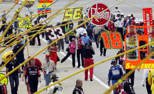 Race fans walk along pit road prior to the NASCAR Sprint Cup Series auto race at Talladega Superspeedway in Talladega, Ala., Sunday, May 6, 2012. (AP Photo/Dave Martin)