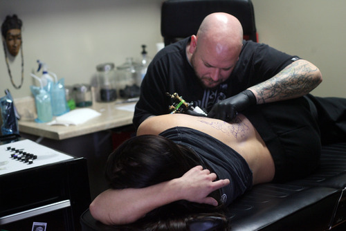 Kim Raff I The Salt Lake Tribune Darrell Palmer gave Krys Maki a tattoo at Lucky Bamboo Tattoo in Layton in December. The Davis County Board of Health has approved tighter standards for body art businesses, with many of the changes at the request of tattoo artists themselves.