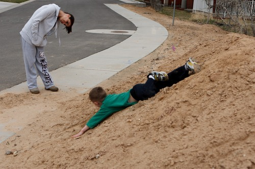 Trent Nelson  |  The Salt Lake Tribune Jen Carver looks on as her son T.J. slides down a pile of dirt near their home Wednesday, March 28, 2012 in Ogden, Utah. U.S. Army veteran Jen Carver served two tours in Iraq and is now a full time college student with an on-campus job while raising her 4-year-old son. After a long day of school and work, Carver keeps her evenings as,