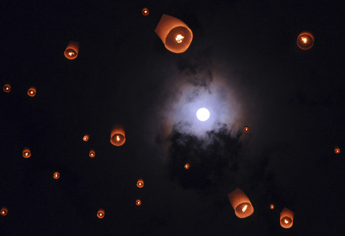 In this late Sunday, May 6, 2012 photo, lanterns release by Buddhist worshippers fly as full moon is seen in the background during a procession commemorating Waisak day which marks the birth, death and enlightenment of Buddha at the 9th century Borobudur temple in Magelang, Central Java, Indonesia. (AP Photo/Slamet Riyadi)