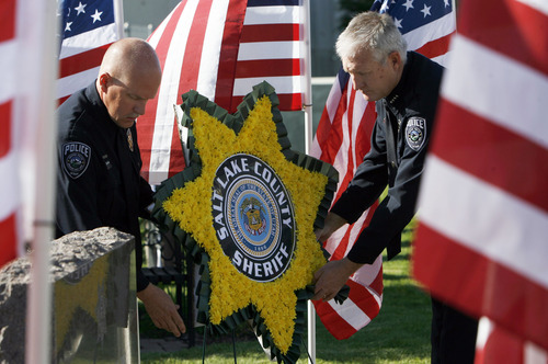 Francisco Kjolseth  |  The Salt Lake Tribune Officer A.J. Morley, left, and Sheriff James M Winder, on Wednesday present the laying of the wreath as Salt Lake County Sheriff's and Unified Police honor fallen members at a memorial service during a short program at the Salt Lake County Sheriff's Office.
