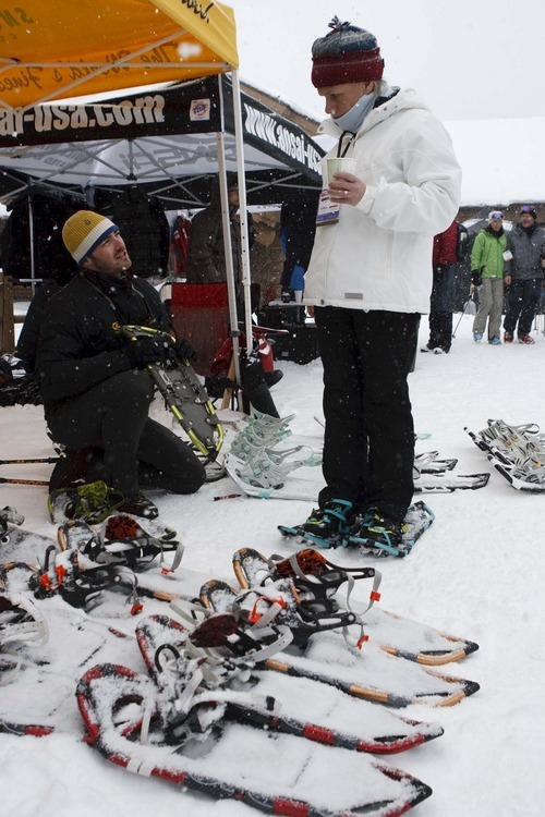 Trent Nelson  |  The Salt Lake Tribune Connor Folley, Marketing Manager for K2 Outdoor, fits Els Fonteyne with a pair of snow shoes at Mountain Demo Day, which kicked off the Outdoor Retailer Winter Market trade show Wednesday at Solitude Mountain Resort. Attendees were able to examine and try out the latest in winter sports equipment.