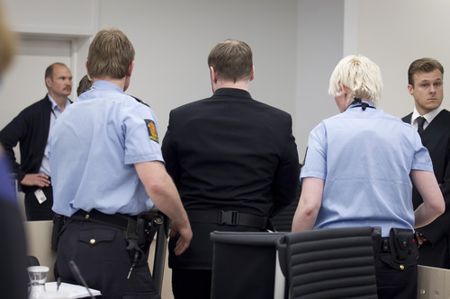 The self-styled, anti-Muslim militant Anders Behring Breivik, centre, is escorted from the courtroom by police following an incident when a shoe was thrown at Breivik, in Oslo Friday, May 11, 2012.  The trial of Breivik was interrupted briefly Friday when the brother one of his 77 victims hurled a shoe at the confessed mass killer and yelled,