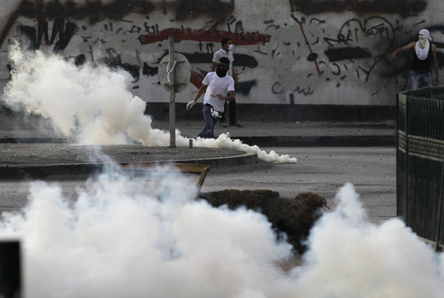 Anti-government demonstrators are seen in front of a wall painted with anti-government graffiti and blacked out by authorities many times over during clashes with riot police firing tear gas Saturday, May 12, 2012, in Bilad al-Qadeem, Bahrain, on the outskirts of the capital of Manama. Clashes erupted during a protest demanding democracy and freedom for political prisoners, one of several such demonstrations Saturday. (AP Photo/Hasan Jamali)