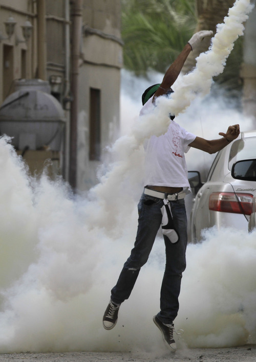 An anti-government demonstrator throws a tear gas canister back toward riot police who fired it Saturday, May 12, 2012, in Bilad al-Qadeem, Bahrain, on the outskirts of the capital of Manama. Clashes erupted during a protest demanding democracy and freedom for political prisoners, one of several such demonstrations Saturday. (AP Photo/Hasan Jamali)