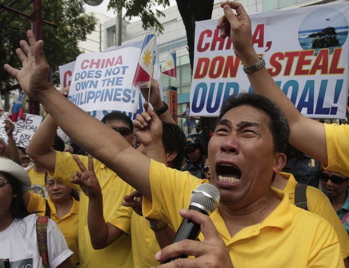 A protester delivers his message during a rally in front of the Chinese consulate Friday, May 11, 2012 in Manila's financial district of Makati, Philippines. The Philippines and China are in a standoff over Scarborough Shoal which began early April after the Philippine navy accused Chinese boats of illegally fishing in the area. The protesters called on the Chinese government to pull out its vessels in the area and asserted that the shoal is part of Philippine territory. (AP Photo/Pat Roque)