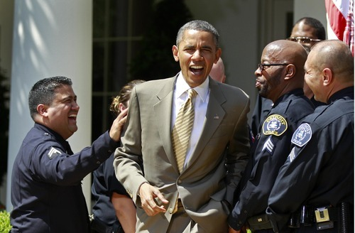 President Barack Obama shares a laugh with a group of law enforcement officers after honoring them as the 2012 National Association of Police Organizations TOP COPS award winners Saturday, May 12, 2012, during a Rose Garden ceremony at the White House in Washington. (AP Photo/Haraz N. Ghanbari)