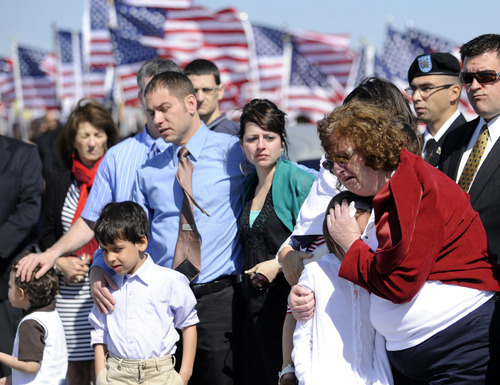 Family members grieve as the body of U.S. Army Capt. Bruce Kevin Clark who died in Afghanistan is carried across the tarmac during Military honors at Rochester International Airport Saturday, May 12, 2012 in Rochester, N.Y.  Military officials say Clark's wife, Susan Orellana-Clark, was in Texas Skyping with him on April 30 when he collapsed. Army officials say the investigation into the death is continuing. (AP Photo/Gary Wiepert) (AP Photo/Gary Wiepert)