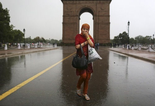 An Indian girl reacts as she runs from a sudden thundershower at the India Gate monument in New Delhi, India, Saturday, May 12, 2012. (AP Photo/Kevin Frayer)