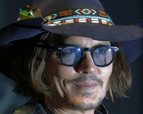 Actor Johnny Depp poses at a news conference to promote his new film