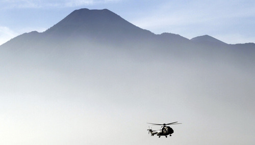 An Indonesian helicopter carrying the bodies of victims of Wednesday's plane crash flies through Bogor, in West Java, Indonesia. Clearer weather finally allowed Indonesian helicopters to land Saturday and retrieve some remains of the 45 people aboard a Russian-made plane that crashed into the volcano during a demonstration flight. (AP Photo/Achmad Ibrahim)
