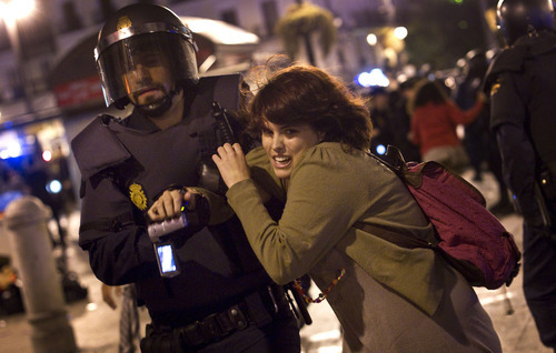 A woman is led away by a police officer at Puerta del Sol square in Madrid, Spain, Sunday, May 13, 2012. Police officers have evicted people gathered in an assembly at Sol square during the early hours. Spaniards angered by increasingly grim economic prospects and unemployment hitting one out of every four citizens protested in droves Saturday in the nation's largest cities, marking the one-year anniversary of a spontaneous movement that inspired similar anti-authority demonstrations across the planet. (AP Photo/Alberto Di Lolli)