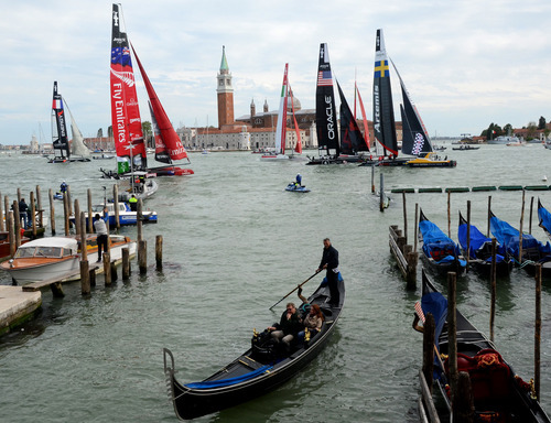 A gondola quietly passes in foreground as multihulls compete in the America's Cup World Series, in Venice, Italy, Sunday, May 13, 2012. (AP Photo/Luigi Costantini)