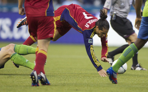 Real Salt Lake's Fabian Espíndola is tripped up during the second half of play against the Seattle Souders FC in a MLS soccer match, Saturday, May 12, 2012, in Seattle. Real Salt Lake won the match 1-0. (AP PHOTO/Stephen Brashear)