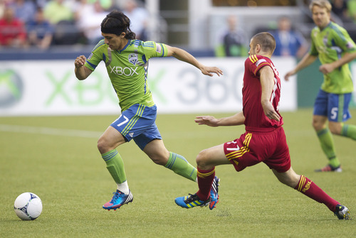 Sounders' Fredy Montero, left, streaks away from Real Salt Lake's Chris Wingert during the first half of play in a MLS soccer match, Saturday, May 12, 2012, in Seattle. (AP PHOTO/Stephen Brashear)