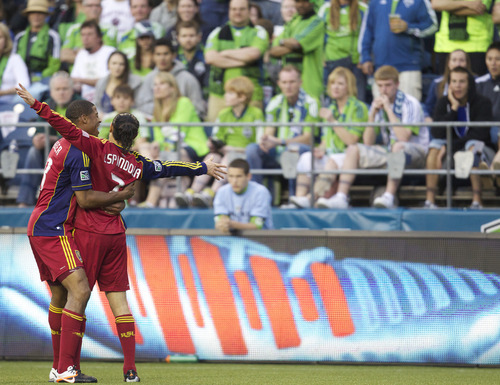 Real Salt Lake's Fabian Espindola, right, gets a hug from teammate Chris Schuler after Espindola scored a goal against the Seattle Souders FC during the second half of play in a MLS soccer match, Saturday, May 12, 2012, in Seattle. Real Salt Lake won the match 1-0. (AP PHOTO/Stephen Brashear)