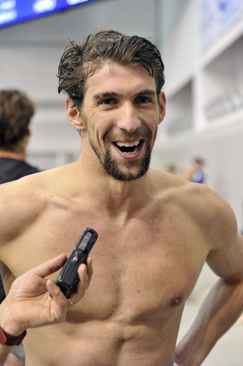 Michael Phelps talks with reporters after winning the men's 100 meter butterfly final at the Austin Grand Prix swimming meet Friday, Jan. 13, 2012, in Austin, Texas. (AP Photo/Michael Thomas)