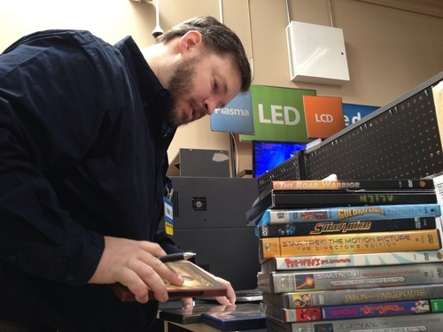 Richard Zimmerman, electronics department manager for a Walmart in Sandy sifts through a stack of DVD movies for a customer to unlock a digital version of those movies. Walmart's