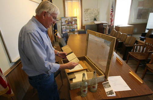 Steve Griffin/The Salt Lake Tribune   Milton Hanks, mayor of Eureka, looks through some city memorabilia including Salt Lake Brewing Company beer bottles and liquor receipts from the old bars at the Eureka City Offices.