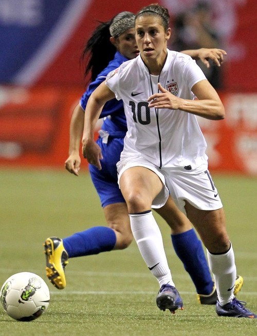 United States' Carli Lloyd (10) controls the ball ahead of Dominican Republic's Jocelin Rodriguez (15) during the first half of a CONCACAF women's Olympic qualifying soccer match in Vancouver, British Columbia, Friday, Jan. 20, 2012.  (AP Photo/The Canadian Press, Jonathan Hayward)