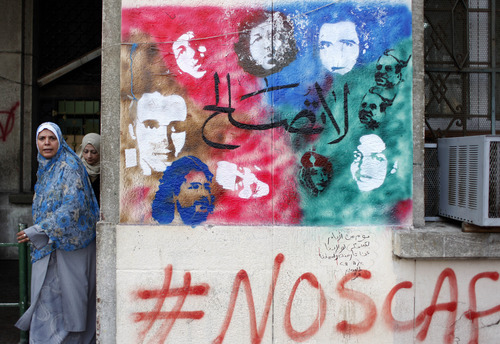 FILE - In this Tuesday, Dec. 20, 2011 file photo, two women walk next to a mural depicting the faces of some of the people killed before and after the revolution at Tahrir Square in Cairo, Egypt. Arabic writing at center reads