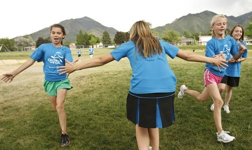 Leah Hogsten  |  The Salt Lake Tribune Mentor Emeliee Dirks (center)  congratulates Nellie Orme (left) and Lauren Dirks (right) as the girls finish running.  Morningside Elementary 3rd -6th grade girls run into shape after school for a 5k run with the guidance of  trained coaches that mentor the girls Wednesday, May 16 2012 in Salt Lake City..  Girls on the Run is a national non-profit in 43 states. The 12-week program concludes with all participants walking or running in a 5K (3.1 mile) event.