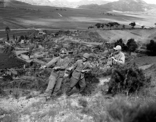 U.S. 25th Division soldiers string wire around the perimeter of their hilltop position won from the enemy on the Korean front on Sept. 1, 1950. Burned out village lies in valley below. Pulling barbed wire into position are (left to right), Cpl. Darrell Beckstead, Salt Lake City; Pfc Fred Sinolair, Roxbury, Mass., and Sgt. Richard W. Bean, Berlin, N.H. (AP Photo/Max Desfor