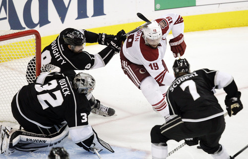 Phoenix Coyotes right wing Shane Doan (19) tries to score as he is defended by Los Angeles Kings defenseman Drew Doughty (8), Rob Scuderi (7) and goalie Jonathan Quick (32) during the second period of Game 4 of the NHL hockey Stanley Cup Western Conference finals in Los Angeles, Sunday, May 20, 2012. (AP Photo/Jae C. Hong)