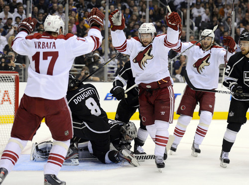 Phoenix Coyotes right wing Shane Doan, center, celebrates his goal with right wing Radim Vrbata, left, of the Czech Republic, and center Martin Hanzal, of the Czech Republic, as Los Angeles Kings defenseman Drew Doughty, second from left, and goalie Jonathan Quick sit in front of the goal during Game 4 of the NHL hockey Stanley Cup Western Conference finals, Sunday, May 20, 2012, in Los Angeles. (AP Photo/Mark J. Terrill)
