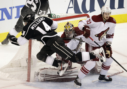 Los Angeles Kings' Justin Williams (14) falls to ice in front of Phoenix Coyotes goalie Mike Smith, center, and Oliver Ekman-Larsson, of Sweden, during the first period of Game 4 of the NHL hockey Stanley Cup Western Conference finals in Los Angeles, Sunday, May 20, 2012. (AP Photo/Jae C. Hong)